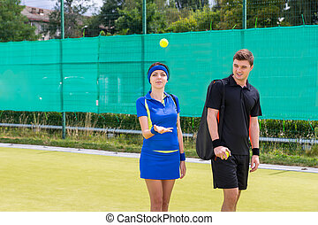 Woman tennis-player throwing tennis ball near her partner on a court outdoor in summer or spring