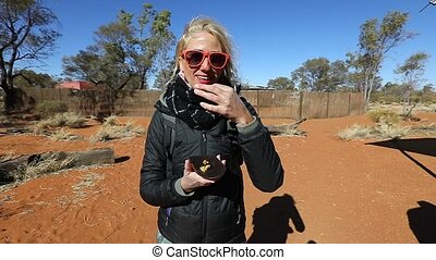 SLOW MOTION: Tourist woman testing a Witchetty grubs that feeds on the roots of witchetty bush common in Northern Territory, Australia. The grub was the main food of diets of Aboriginal Australians.