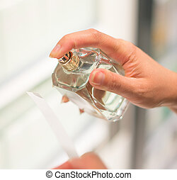 Woman testing perfume in the shop.