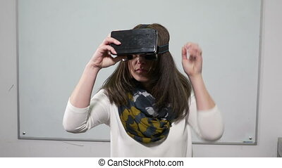 Woman testing virtual reality glasses in a classroom with whiteboard behind
