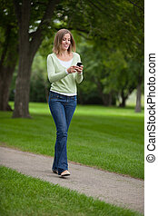 Woman Text Messaging In Park