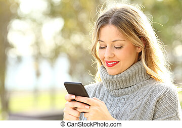 Woman texting on a smart phone in winter