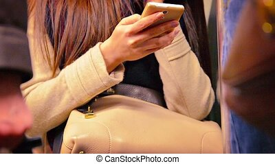Woman Texting on her Smart Phone in the Subway