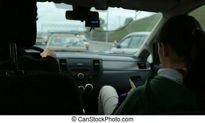 Woman texting on mobile phone at car