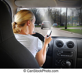 A young woman is on the cell phone textign and driving with a road in the windshield for an danger or distracted driving concept.