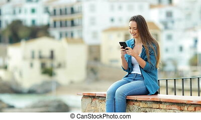 Woman texting on phone and looks away - Happy woman texting...
