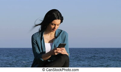Woman texting on smart phone on the beach - Serious woman...