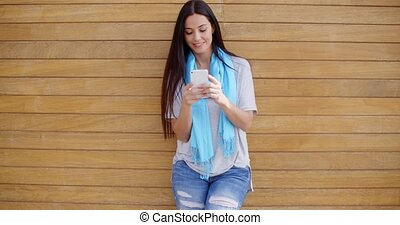 Woman texting while leaning against wall - Smiling young...