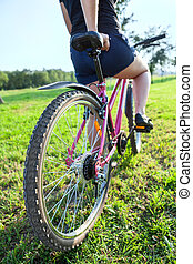 Woman the cyclist on mountain bike in city park