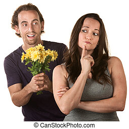 Young woman thinking about forgiving man with flowers