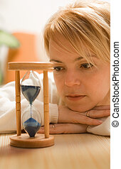 Young woman contemplating by an hourglass, propping her head - shallow DOF