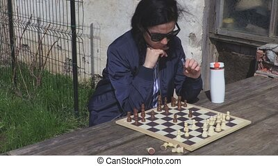 Woman thinking near chess board