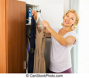 Woman thinking what get dressed - Mature smiling woman at...