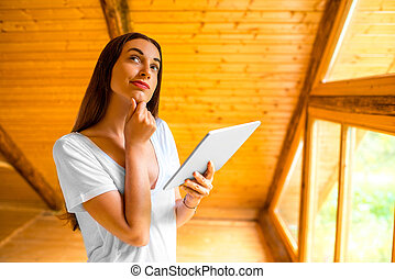 Woman thinking with digital tablet in the wooden house