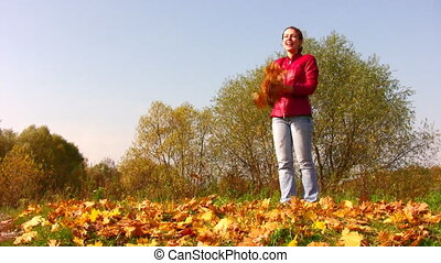 woman throw autumn leaves