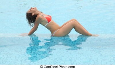 Woman throw back one's head cuit sits in pool shallow water