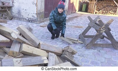 Woman throw firewood in pile