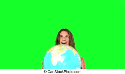 Woman throwing a globe in the air o
