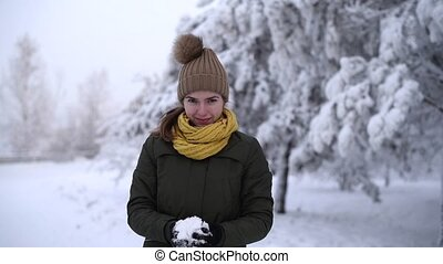 Woman throwing a snowball into the camera - Beautiful woman...