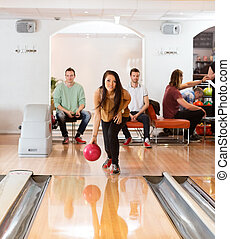 Woman Throwing Bowling Ball in Club