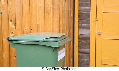 Woman throwing garbage into litter-box in outside and...