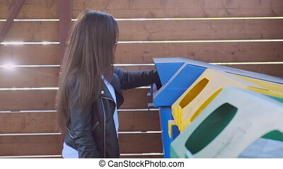 Woman throwing garbage paper cap to recycling dumpster