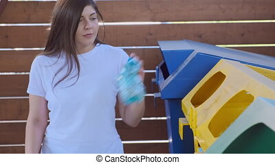 Woman throwing garbage paper cap to recycling dumpster and she is looking at the camera and smiling