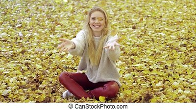 Woman throwing leaves - Pretty happy-looking woman sitting...