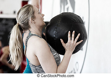 Woman Throwing Medicine Ball In Gym
