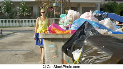 Woman passing by overfull street recycle bins and throwing a plastic bottle in one of them. problem of garbage utilization