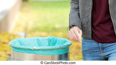 Woman throwing trash into bin in a park - Close up of a...