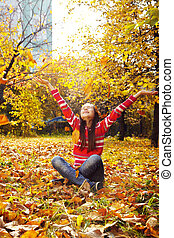 woman throwing up yellow leaves
