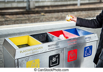 Woman throws paper trash in the trash sorting waste