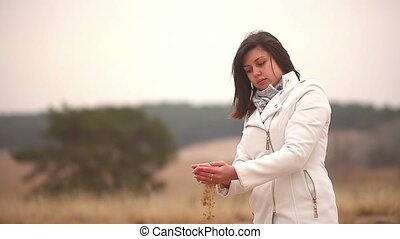 Woman throws sand symbol time autumn cold nature