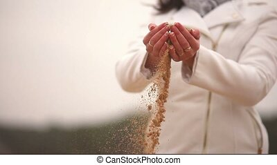 Woman throws sand symbol time autumn nature close-up cold