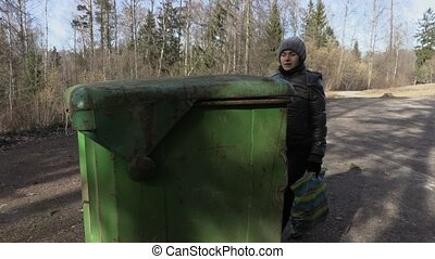Woman throws waste out in garbage container