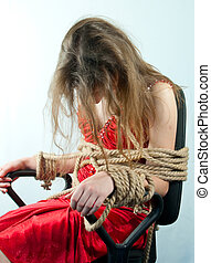Woman tied up with a rope against light background