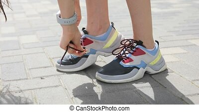 Woman stops and ties shoelaces and runs for jogging, feet closeup. Girl is jogging in sneakers in pavement on the city street.