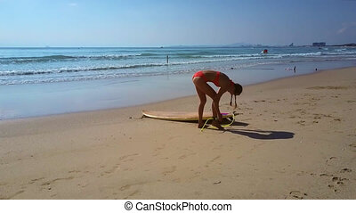 woman ties surfboard rope to leg against pictorial seascape...