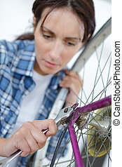 Woman tightening bicycle wheel nut with wrench