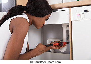 Woman Tightening Sink Pipe With Monkey Wrench