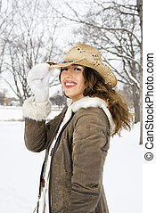 Caucasian young adult female smiling and tilting straw cowboy hat at viewer.