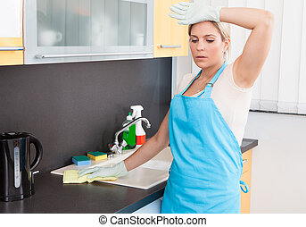Woman Tired Cleaning Kitchen Worktop At Home