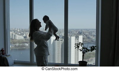 Woman tossing baby up