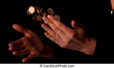 Woman tossing euro coins on black background
