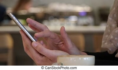 Woman touch smartphone screen in a cafe