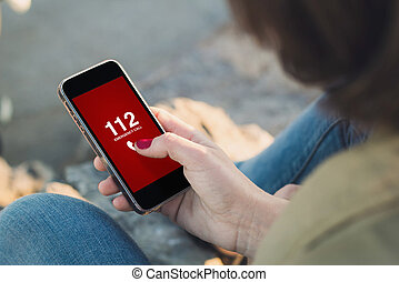 Woman touch the screen of her smartphone dialing emergency phone number