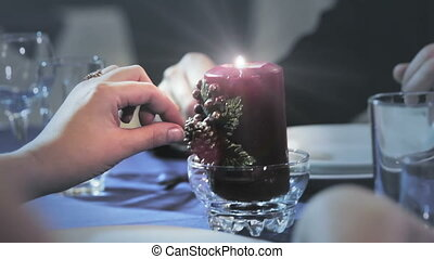 woman touches a candle on the table
