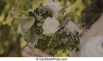 Woman touches a wedding bouquet on a sunny day