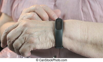 Woman touches on the wristband of pulse monitor - Wristband...